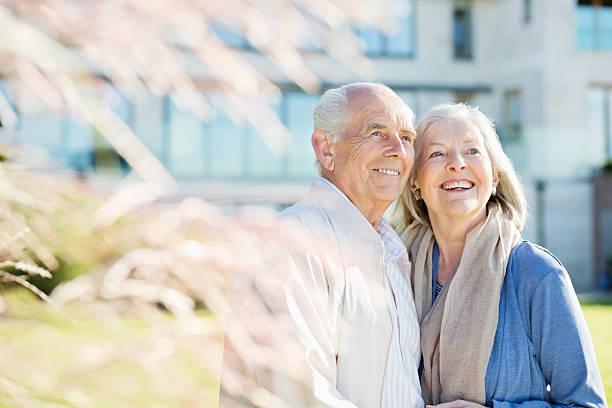 Couple de seniors qui sourit devant sa maison de retraite
